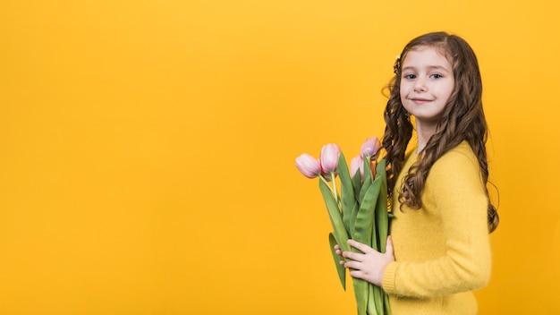 Nettes mädchen, das mit rosa tulpen steht