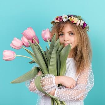 Nettes mädchen, das mit rosa tulpenblumen steht