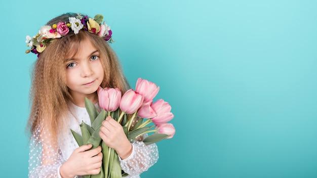 Nettes mädchen, das mit tulpenblumen steht