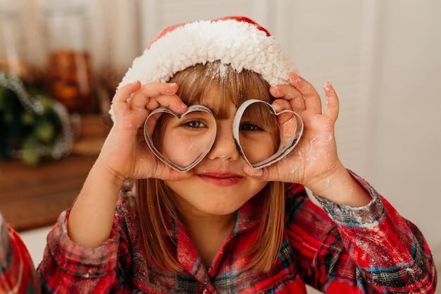 Nettes mädchen, das mit weihnachtsplätzchenformen spielt