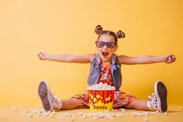 Nettes mädchen, das popcorn isst