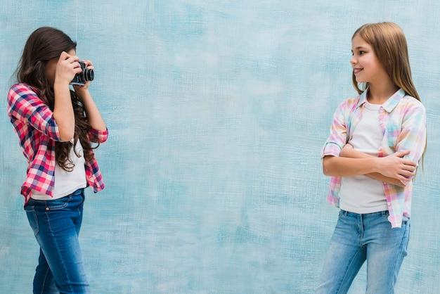 Nettes mädchen, das vor ihrem freund aufwirft ihr foto mit kamera gegen blauen hintergrund aufwirft