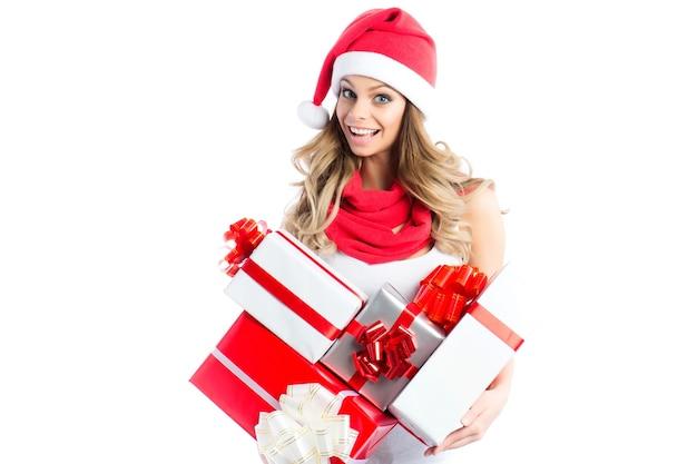 Nettes mädchen, das weihnachts- und neujahrsgeschenke hält. weihnachtsmädchen in der weihnachtsmütze mit den kästchen lokalisiert.