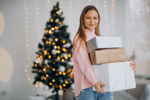 Nettes mädchen, das weihnachtsgeschenke durch weihnachtsbaum hält