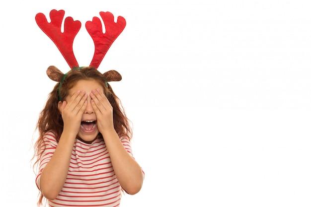Nettes mädchen, das weihnachtsgeweihe und -c $ weinen trägt