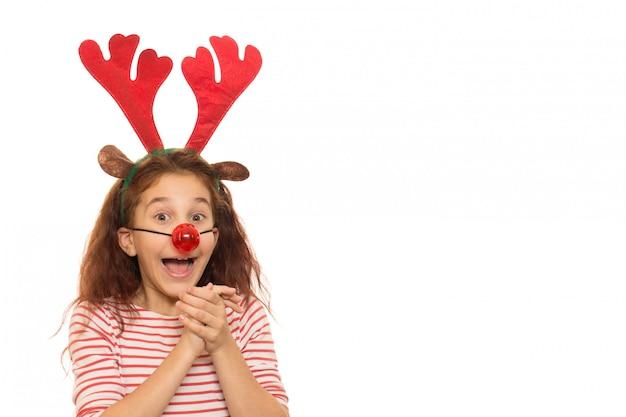 Nettes mädchen, das weihnachtsgeweihe und rote wekzeugspritze trägt