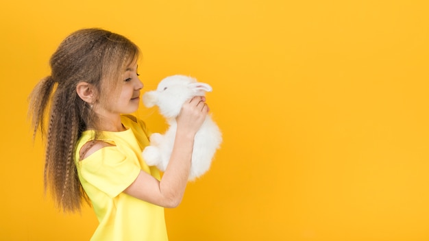 Nettes mädchen, das weißes kaninchen betrachtet