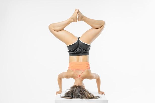 Nettes mädchen, das yoga auf weiß lokalisiert tut
