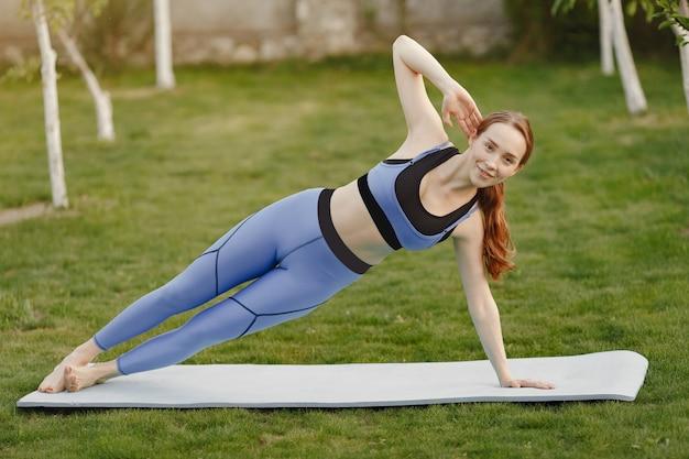 Nettes mädchen, das yoga in einem sommerpark tut
