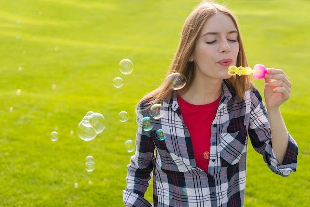 Nettes mädchen der vorderansicht, das seifenblasen bildet
