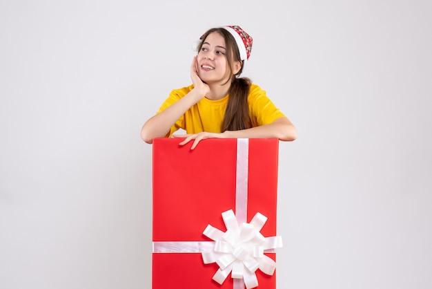 Nettes mädchen der vorderansicht mit weihnachtsmütze, die etwas betrachtet, das hinter großem weihnachtsgeschenk tanding