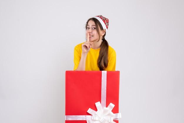 Nettes mädchen der vorderansicht mit weihnachtsmütze, die shh zeichen macht, das hinter großem weihnachtsgeschenk steht