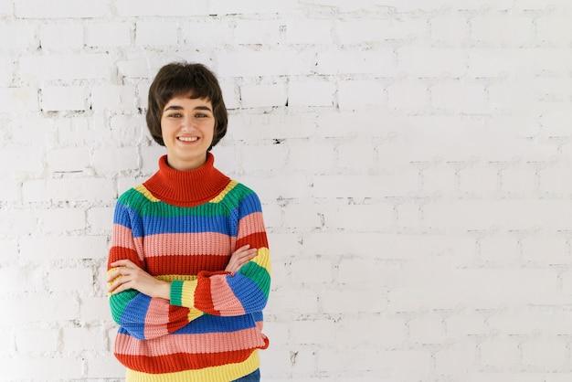 Nettes mädchen des porträts in der regenbogenstrickjacke gegen weißen backsteinmauerhintergrund. junge kaukasische frauen, die die kamera betrachten und lächeln. lgbt-konzept.