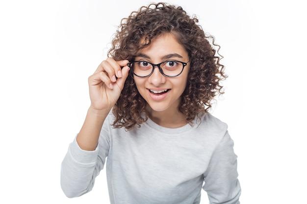 Nettes mädchen des porträts mit den gläsern, die bedacht die kamera auf weiß lokalisiert untersuchen.
