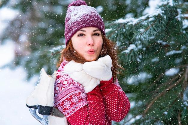 Nettes mädchen, frau schickt einen, um einen kuss zu blasen. romantische frau, frau, die winterschlittschuhe auf ihrer schulter hält. winteraktivitäten und sport.