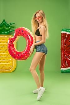 Nettes mädchen im badeanzug, das im studio mit aufblasbarem schwimmkreis aufwirft. sommerporträt kaukasischer teenager auf grün