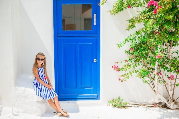 Nettes mädchen im blauen kleid an der straße des typischen griechischen traditionellen dorfs mit weißen wänden und bunten türen auf mykonos-insel, in griechenland