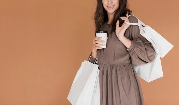 Nettes mädchen im kleid mit kaffee und vielen einkaufsnetzen