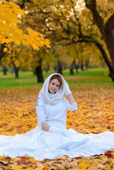 Nettes mädchen im langen weißen hochzeitskleid, das im ländlichen weg unter herbstlichen bäumen im wald in der goldenen stundenatmosphäre aufwirft.