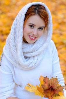 Nettes mädchen im langen weißen hochzeitskleid, das im ländlichen weg unter herbstlichen bäumen in der goldenen stundenatmosphäre aufwirft.