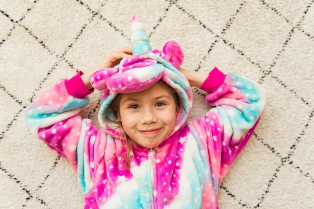 Nettes mädchen im rosa kigurumi-einhorn-pyjama-kostüm