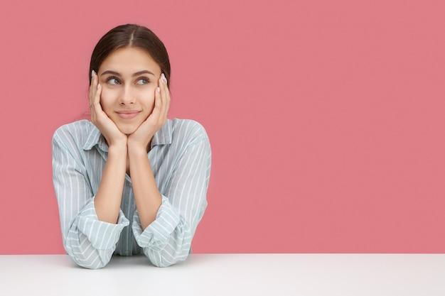 Nettes mädchen im stilvollen gestreiften hemd, das an ihrem arbeitsplatz mit ellbogen auf schreibtisch sitzt, gesicht auf händen kissen, mit gelangweiltem oder nachdenklichem gesichtsausdruck wegschauend, denkend, wie man sich unterhält