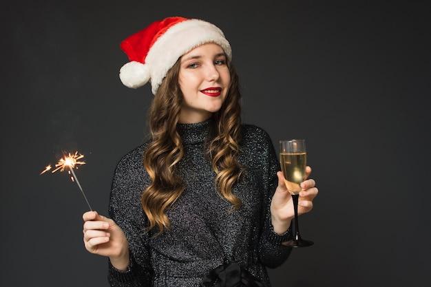 Nettes mädchen im weihnachtsmann-hut feiert weihnachten und neues jahr
