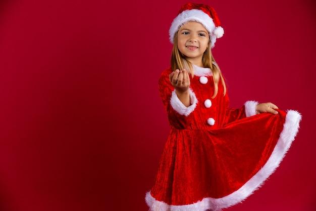 Nettes mädchen im weihnachtsmannkostüm und in der wintermütze. kind mit blonden haaren und braunen augen, das hält