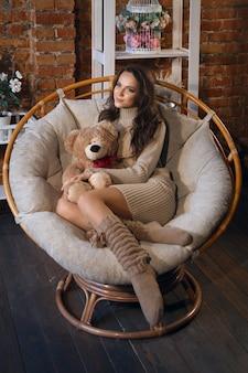 Nettes mädchen in den kniestrümpfen und in der strickjacke mit teddybären in ihren händen, die im lehnsessel im fantastischen raum sitzen