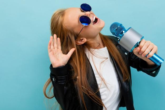 Nettes mädchen in der schwarzen jacke, blaue sonnenbrille singt lieder mit blauem mikrofon lokalisiert auf blauem hintergrund