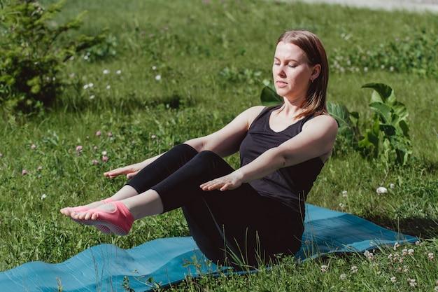 Nettes mädchen in der schwarzen kleidung auf dem grünen gras, das yoga tut. sportlicher lebensstil