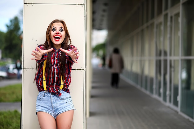 Nettes mädchen in einem clown-make-up auf dem hintergrund einer messe und schritte