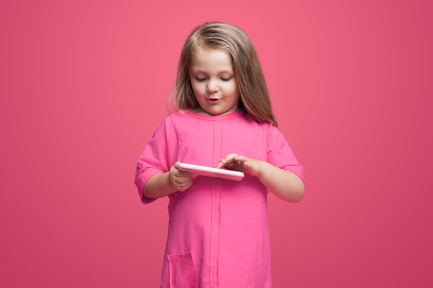 Nettes mädchen in einem roten kleid spielt mit einer tafel an einer wand, die den bildschirm berührt und lächelt
