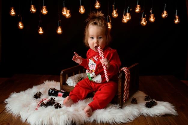 Nettes mädchen in einem roten weihnachtskostüm mit retro-girlanden sitzt auf einem fell