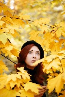 Nettes mädchen in gelbem laub schaut auf das romantische porträt der herbstbäume im herbst eines rothaarigen ...
