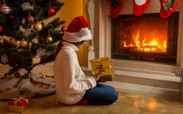 Nettes mädchen in weißem pullover und weihnachtsmütze, das mit weihnachtsgeschenk am kamin sitzt