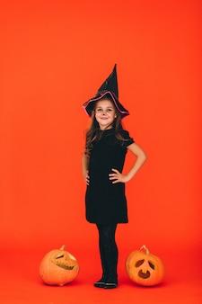 Nettes mädchen kleidete im halloween-kostüm im studio an