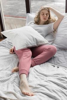 Nettes mädchen kleidete in den rosa pyjamahosen und in weißem t-shirt an, die auf bett mit kissen nahe fenster liegen