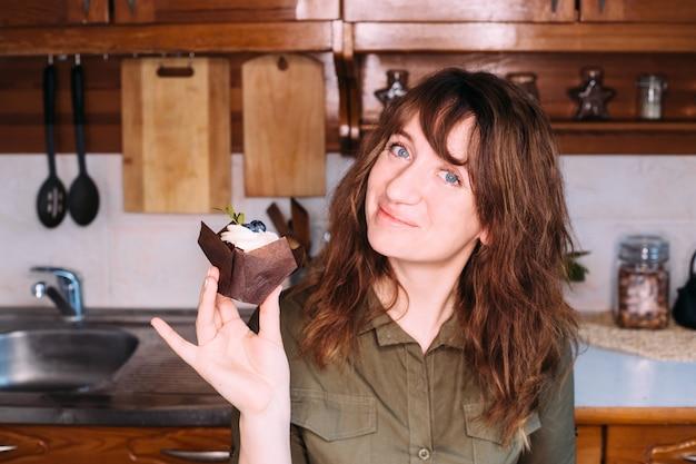 Nettes mädchen lächelt und hält cupcake und schneebesen in der wohnküche.