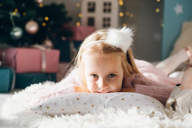Nettes mädchen liegt auf ihrem bauch auf einem kissen nahe einem weihnachtsbaum