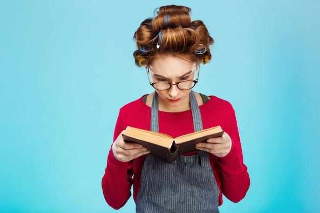 Nettes mädchen liest buch, das brille mit lockenwicklern auf haar trägt
