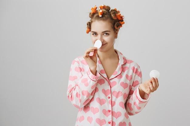 Nettes mädchen-make-up vor dem schlafengehen mit wattepad, lockenwickler und pyjama tragend