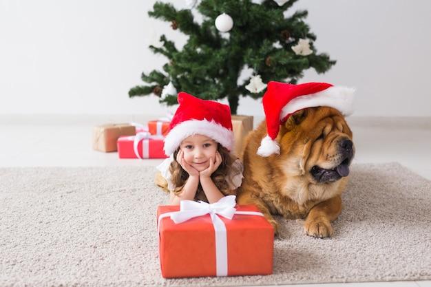 Nettes mädchen mit chow-hund, der nahe dem weihnachtsbaum sitzt