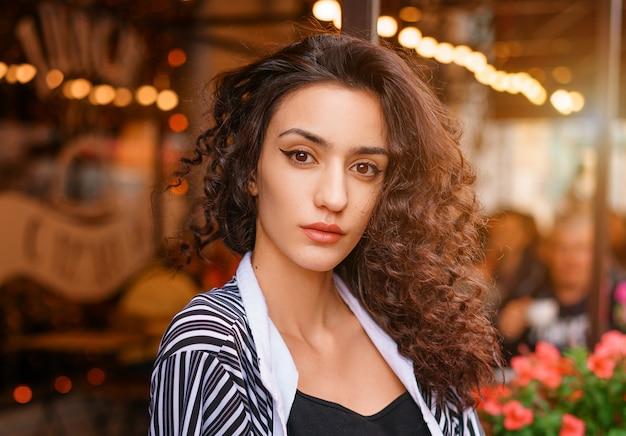 Nettes mädchen mit dem gewellten haar, porträt eines mädchens in einem café.