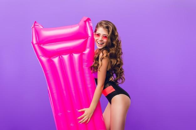 Nettes mädchen mit dem langen lockigen haar in der rosa sonnenbrille lächelt zur kamera auf lila hintergrund. sie trägt einen badeanzug und hält eine rosa luftmatratze.