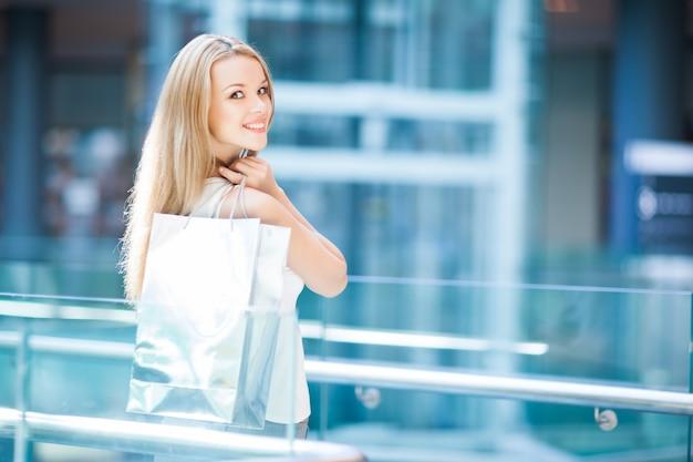 Nettes mädchen mit den blonden haaren, die lächeln und weiße einkaufstasche im einkaufszentrum halten. mit dem rücken gedreht posieren und in die kamera schauen