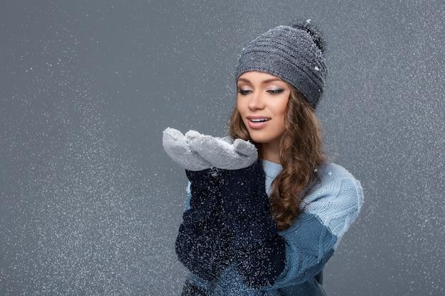 Nettes mädchen mit den schneeflocken, die eine gute zeit haben