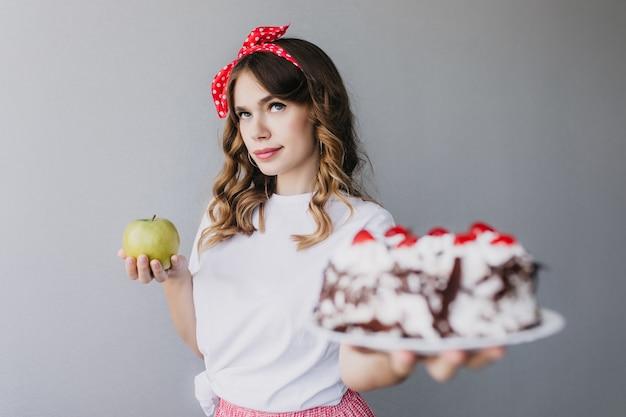 Nettes mädchen mit dunklem welligem haar, das an kalorien denkt und kuchen hält. innenfoto der gutaussehenden jungen frau mit apfel und cremigem schokoladenkuchen.