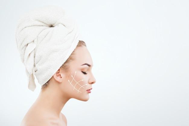 Nettes mädchen mit dunklen augenbrauen und nackten schultern, tragendes weißes handtuch auf kopf nach unten schauend, ein modell mit hellem nacktem make-up, weißem studiohintergrund, schönheitsfoto, profilporträt