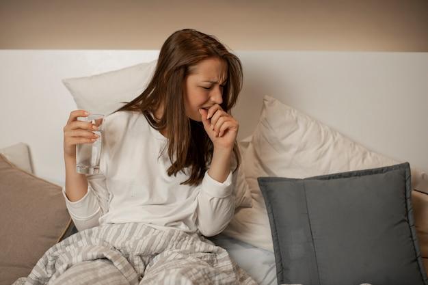 Nettes mädchen mit einem glas wasser kann nicht schlafen, sitzt im bett, fühlt sich unwohl und hustet